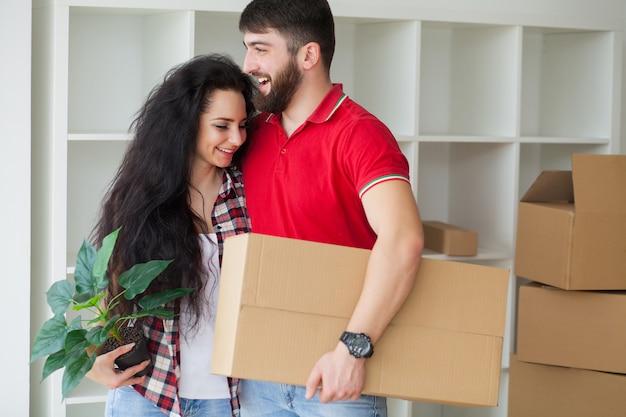 Feliz pareja joven desempacando y mudarse a un nuevo hogar