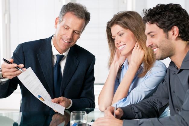 Feliz pareja joven discutiendo con un agente financiero su nueva inversión