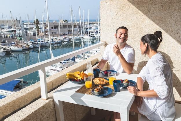 Feliz pareja joven disfrutando del desayuno en la terraza