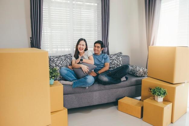 Feliz pareja joven disfrutando juntos moviéndose en una nueva casa.