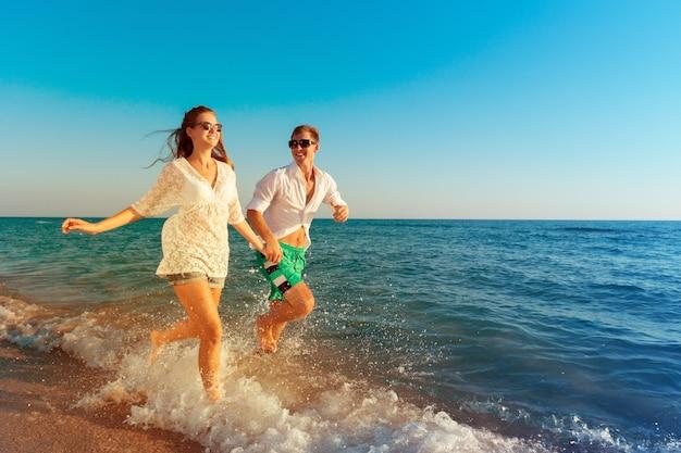 Feliz pareja joven disfrutando del mar