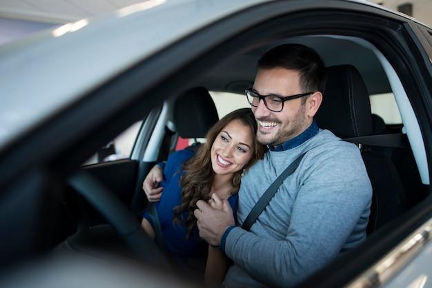Feliz pareja joven disfrutando de su coche nuevo