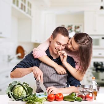 Feliz pareja joven divertirse en la cocina moderna
