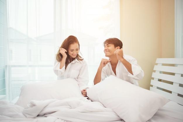 Feliz pareja joven se divierte en la cama
