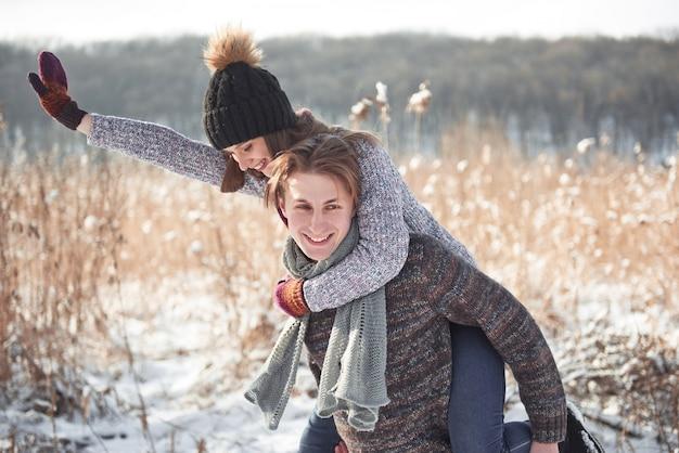 Feliz pareja joven se divierte en la nieve fresca en el hermoso día soleado de invierno de vacaciones