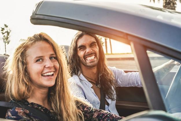 Feliz pareja joven divirtiéndose dentro de coche deportivo convertible - gente de viaje haciendo viaje por carretera en lugar tropical - concepto de vacaciones, viaje y relación - centrarse en la cara del hombre