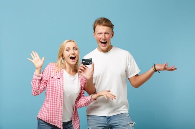 Feliz pareja joven dos amigos chico y mujer en blanco rosa camisetas vacías posando