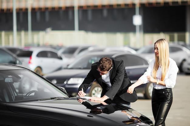 Feliz pareja joven elige y compra un auto nuevo para la familia