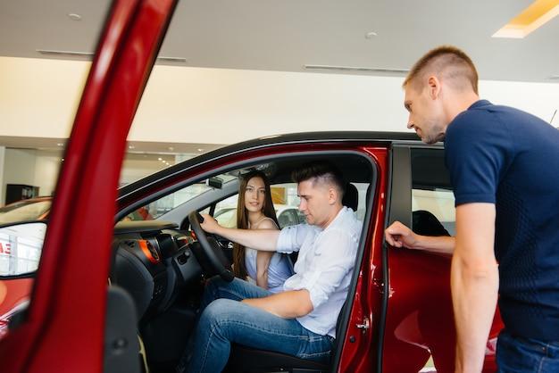 Feliz pareja joven elige y compra un coche nuevo en un concesionario de coches