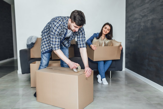 Feliz pareja joven embalaje de cajas de cartón durante la reubicación