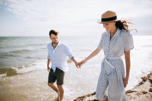 Feliz pareja joven familia caminando por la playa cogidos de la mano. el concepto de luna de miel y vacaciones de verano.