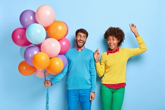 Feliz pareja joven en una fiesta posando con globos