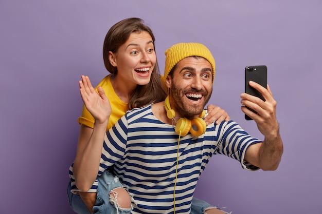 Feliz pareja joven hace una videollamada, sostiene el teléfono inteligente al frente, el chico le da a cuestas a la novia que agita la palma en la cámara del celular, posan juntos contra el fondo púrpura