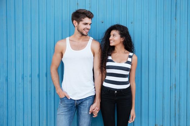 Feliz pareja joven hermosa de pie y cogidos de la mano sobre la pared azul
