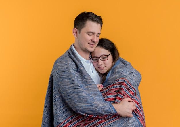 Feliz pareja joven hombre cubriendo con una manta caliente a su novia congelada de pie sobre la pared naranja