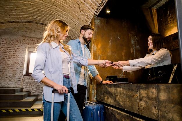 Feliz pareja joven, hombre y mujer, de pie en la elegante recepción del hotel, check-in a la llegada, sonriendo.