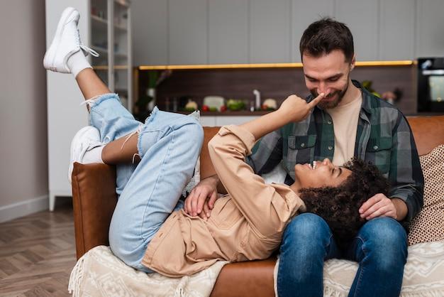 Feliz pareja joven jugando en el sofá