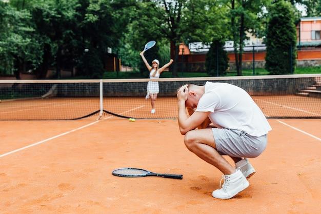 Feliz pareja joven jugar tenis juego al aire libre hombre perdido y mujer tan feliz.
