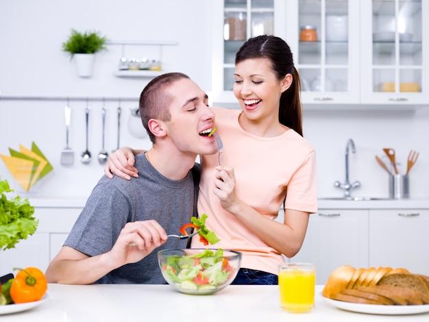 Feliz pareja joven juguetona comiendo juntos en la cocina