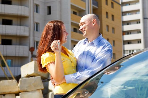 Feliz pareja joven con llaves contra casa de varios pisos