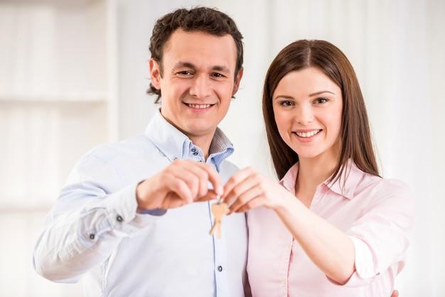 Feliz pareja joven con llaves en su nuevo apartamento.