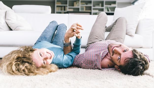 Feliz pareja joven lyind en la alfombra y sonriendo a la cámara