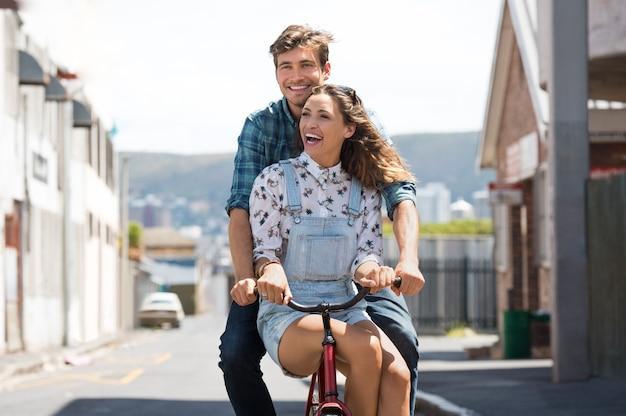 Feliz pareja joven montando en bicicleta juntos