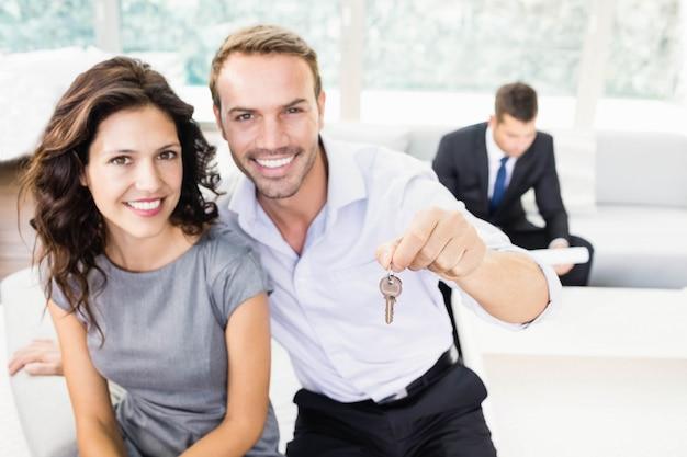 Feliz pareja joven mostrando las llaves de su nueva casa