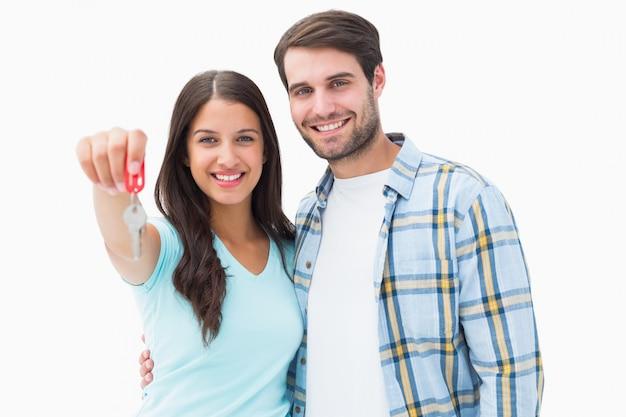 Feliz pareja joven mostrando la nueva llave de la casa