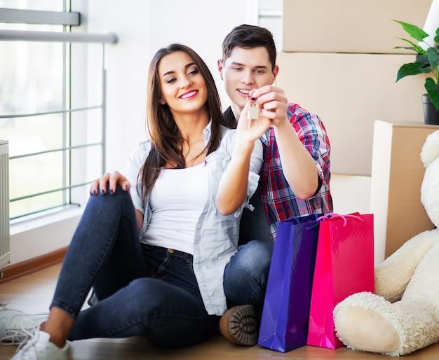 Feliz pareja joven mudarse juntos en apartamento nuevo