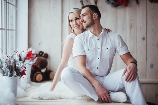 Feliz pareja joven en navidad, hermosos regalos y árbol en el