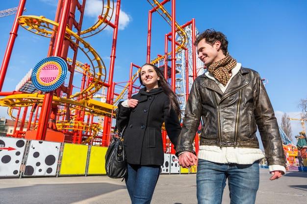 Feliz pareja joven en el parque de atracciones en viena