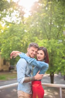 Feliz pareja joven en el parque de pie y riendo en el brillante día soleado