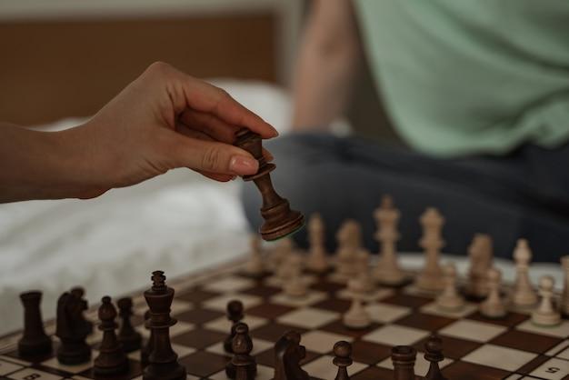 Feliz pareja joven está pasando su tiempo libre jugando al ajedrez, de cerca. familia joven que se muda a un nuevo apartamento.