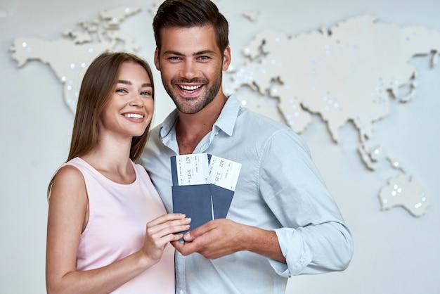 Feliz pareja joven con pasaportes y boletos en la oficina de la compañía de viajes