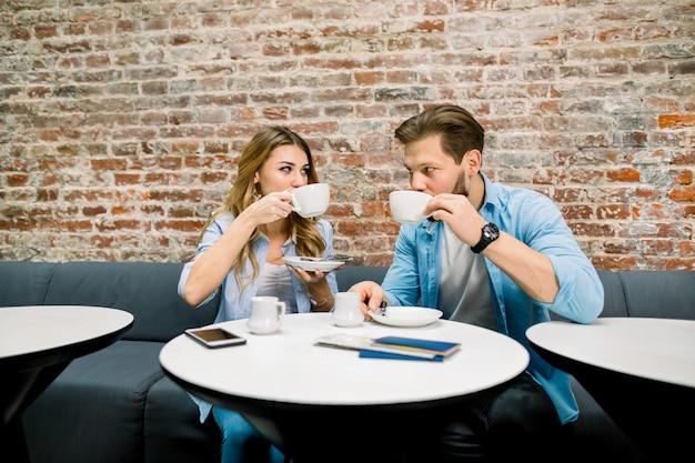 Feliz pareja joven con pasaportes y boletos, sentado en la mesa y tomando café, antes del viaje. hotel lobby cafe, sala de espera