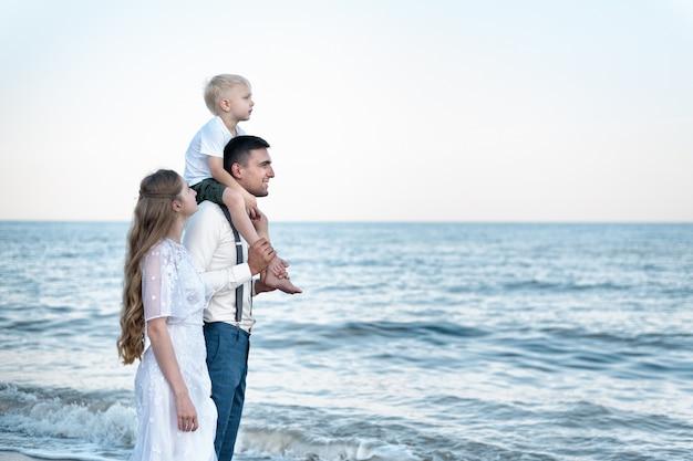 Feliz pareja joven con un pequeño hijo riendo caminando por la playa. vacaciones con el niño