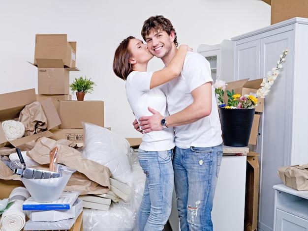 Feliz pareja joven permaneciendo juntos en su nuevo piso común y besos