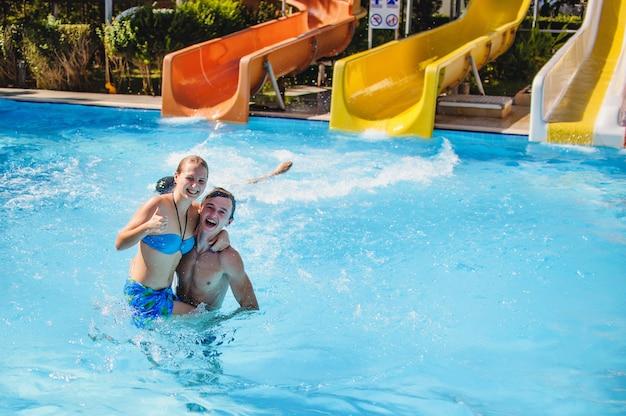 Feliz pareja joven de pie en el agua en la piscina y abrazo. vacaciones de verano, luna de miel.