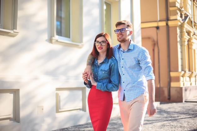 Feliz pareja joven de pie en la calle de la ciudad y riendo en el brillante día soleado
