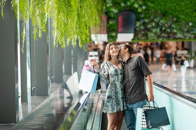 Feliz pareja joven está de pie en la escalera mecánica sosteniendo paquetes con grandes compras en sus manos, el chico besa tiernamente a una niña sonriente. buena compra. grandes compras descuentos