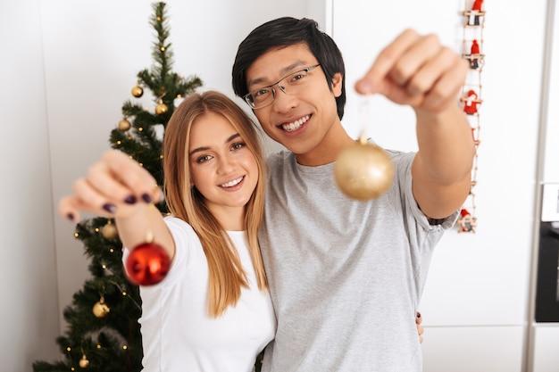 Feliz pareja joven, de pie junto al árbol de navidad en casa, celebrando