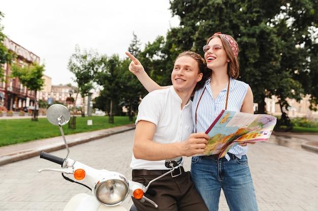 Feliz pareja joven de pie junto con la moto en la calle de la ciudad, analizando el mapa guía de la ciudad