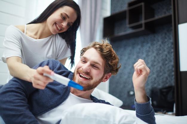 Feliz pareja joven con prueba de embarazo