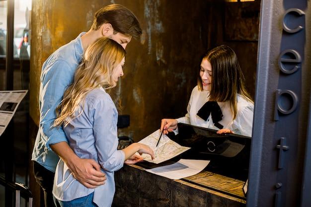 Feliz pareja joven que recibe información turística en la recepción del hotel.