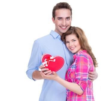 Feliz pareja joven con un regalo en un estudio aislado sobre un fondo blanco.