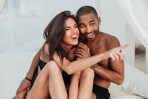 Feliz pareja joven riendo y apuntando lejos en la playa