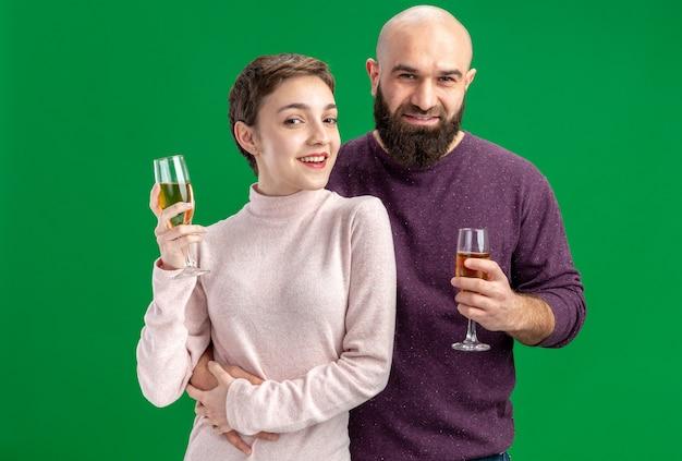 Feliz pareja joven en ropa casual mujer con pelo corto y hombre barbudo con copas de champán felices enamorados juntos celebrando el día de san valentín de pie sobre la pared verde
