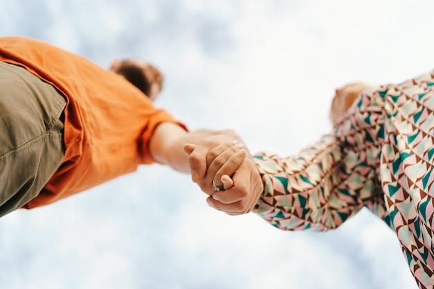 Feliz pareja joven en ropa colorida con cielo