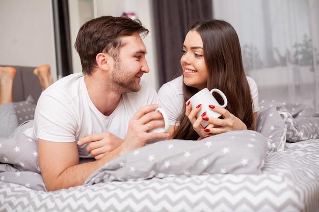 Feliz pareja joven sensual acostado en la cama juntos